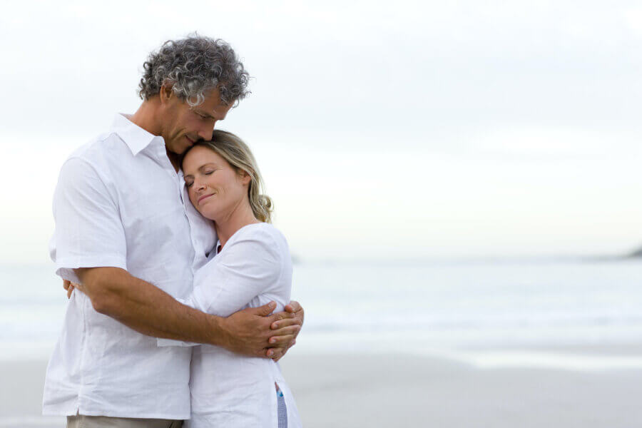 age fertility family planning couple hugging on beach