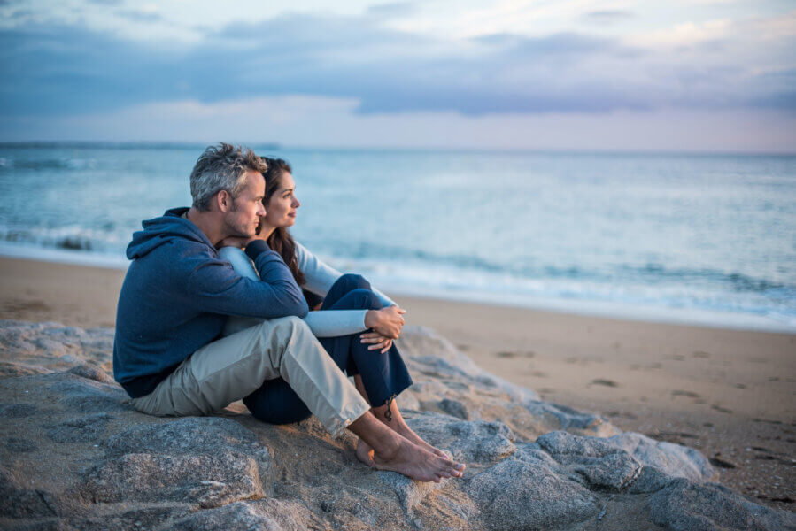 Beautiful couple sitting on a rock at the beach watching the sunset. They wear casual clothes