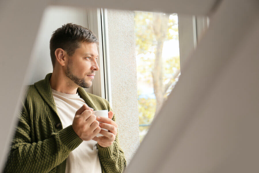 male infertility Man with cup of tea relaxing near window at home