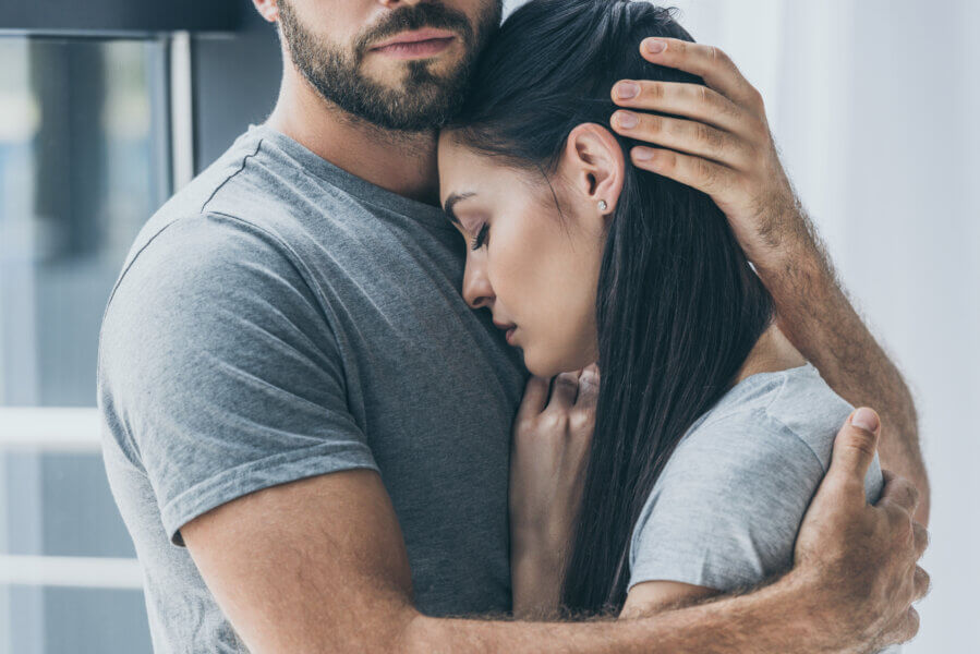 conceive fertility  cropped shot of bearded man hugging and supporting young sad woman