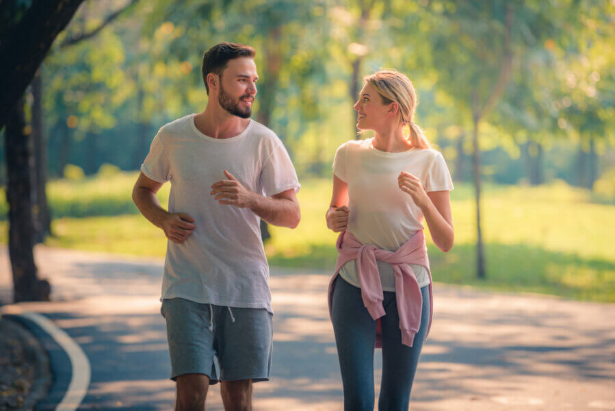 boost fertility Portrait of Young couple running in the park at sunset. Concept sport and love. Warm tone.