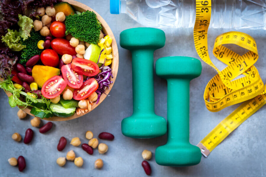 nutrient dense diet and fertility Fresh vegetable salad and healthy food for sport equipment for women diet slimming with measure tap for weight loss on wood background. Healthy Sport Concept